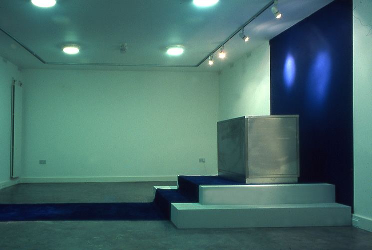 Installation View III, A monitor is fixed horizontally within a stainless steel structure. The steel structure is placed on a series of steps.
